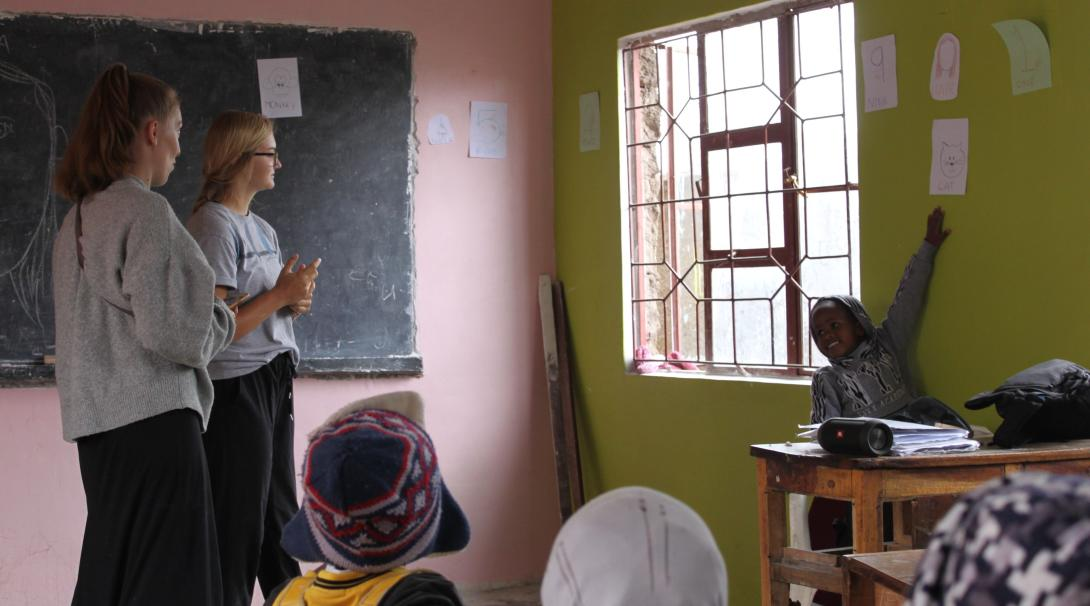Two gap semester students teach a group of young children in Tanzania.
